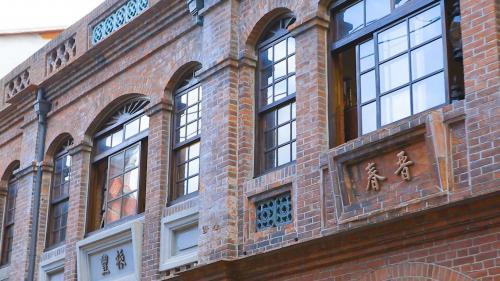 淡水港:簷間有細密的線腳。加有上釉的花瓶欄杆,以上綠釉、藍釉與白釉為主,是台臺灣地區洋樓的常見特色。店面仍以一門兩窗為主,同時加上中式的花鳥紋飾與匾額框。