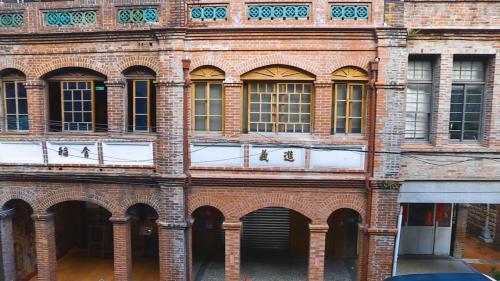 淡水港:清日時期大稻埕特有建築  屋頂上加蓋平直的女兒牆,砌為封閉或鏤空的圖案,或嵌有標示店號的匾額。窗戶拱圈與窗洞結合,有時設置拱廊。