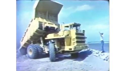 台中港築港抛石作業:將約30部35噸大型卡車從谷關運來的石塊連續傾倒,再用數部D-8推土機推進入海。