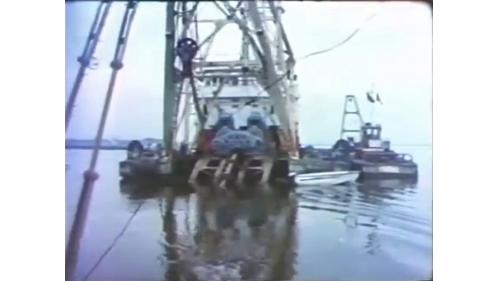 台中港築港挖泥船作業:拋石推進到180公尺,闢建出挖泥船可作業的基本條件,才於第二年挖出勉強可用的航道來拖放沉箱。