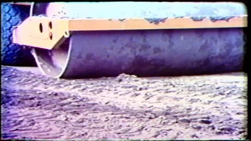 大壩像千層糕般一層層往上填築、灑水、犁土堆平、滾壓夯實,監工人員還要隨時測試密度。